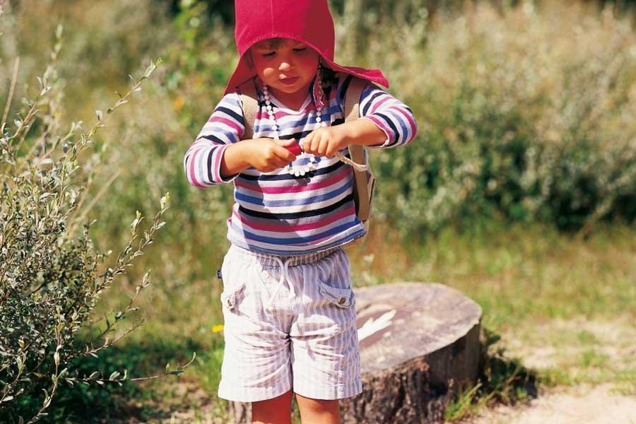 Een klein meisje staat met kaboutermuts op in het bos